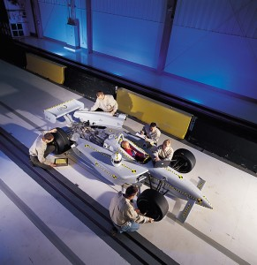 Technicians are shown prepping a race car for a barrier block test.