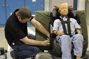 CAPE Test Engineer performs final tasks before conducting a servo sled test on a child car seat.